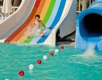 Muchacho en diapositiva en el waterpark Foto de archivo