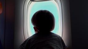 Muchacho en el asiento que mira hacia fuera una ventana del aeroplano metrajes