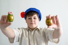 Muchacho en el casquillo nacional ruso con los clavos que sostienen los huevos de Pascua Fotografía de archivo libre de regalías