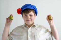 Muchacho en el casquillo nacional ruso con los clavos que sostienen los huevos de Pascua Foto de archivo