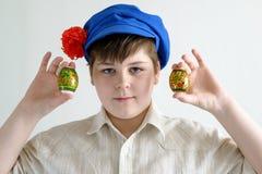 Muchacho en el casquillo nacional ruso con los clavos que sostienen los huevos de Pascua Imagen de archivo