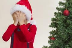 Muchacho en el casquillo rojo de Papá Noel hidding su cara con ambos mano cerca del árbol de navidad Fotografía de archivo