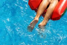 Muchacho en el colchón inflable rojo en piscina Imagen de archivo libre de regalías
