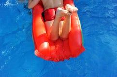 Muchacho en el colchón inflable rojo en piscina Fotografía de archivo