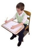 Muchacho en el escritorio de la escuela Fotografía de archivo libre de regalías
