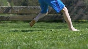 Muchacho en el fútbol de retroceso con el pie en jardín - cámara lenta de la hierba