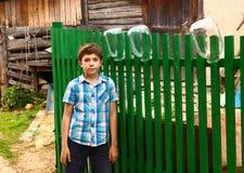 Muchacho en el fondo rural de la cerca del país Imagenes de archivo