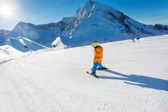 Muchacho en el movimiento en la opinión del esquí de la esquí-pista de la parte posterior imagen de archivo libre de regalías