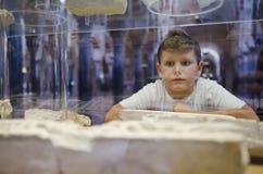 Muchacho en el museo que mira ruinas Imagen de archivo