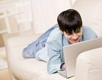 Muchacho en el sofá en sala de estar usando la computadora portátil Fotografía de archivo libre de regalías