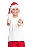 Muchacho en el sombrero de Papá Noel Imagen de archivo