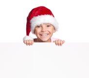 Muchacho en el sombrero de Papá Noel con el espacio en blanco Fotografía de archivo
