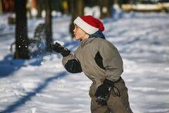 Muchacho en el sombrero de Papá Noel en paseo del invierno en el parque Imagen de archivo libre de regalías