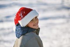 Muchacho en el sombrero de Papá Noel en paseo del invierno en el parque Fotos de archivo