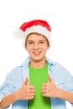 Muchacho en el sombrero de Papá Noel que detiene los pulgares Imagenes de archivo