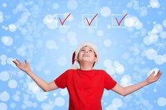 Muchacho en el sombrero de Papá Noel que mira hacia arriba en fondo de la Navidad del día de fiesta Imagen de archivo