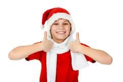 Muchacho en el sombrero de Papá Noel que muestra los pulgares para arriba Fotografía de archivo libre de regalías