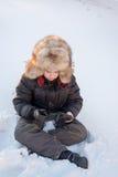 Muchacho en el sombrero del invierno que se sienta en la nieve Fotos de archivo libres de regalías