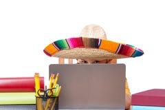 Muchacho en el sombrero rodeado por los libros y el ordenador portátil Fotografía de archivo libre de regalías
