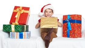 Muchacho en el sombrero rojo con las cajas de regalo - concepto del ayudante de santa del día de fiesta de la Navidad Imagenes de archivo