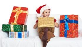 Muchacho en el sombrero rojo con las cajas de regalo - concepto del ayudante de santa del día de fiesta de la Navidad Imagen de archivo libre de regalías