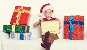 Muchacho en el sombrero rojo con las cajas de regalo - concepto del ayudante de santa del día de fiesta de la Navidad Foto de archivo