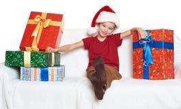 Muchacho en el sombrero rojo con las cajas de regalo - concepto del ayudante de santa del día de fiesta de la Navidad Fotografía de archivo