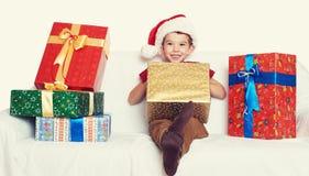 Muchacho en el sombrero rojo con las cajas de regalo - concepto del ayudante de santa del día de fiesta de la Navidad Fotos de archivo