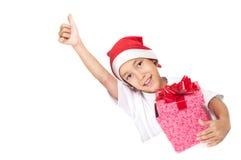 Muchacho en el sombrero rojo de la Navidad que muestra los pulgares para arriba Imagenes de archivo