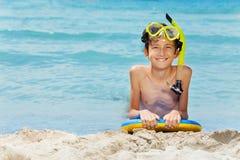 Muchacho en el tablero listo para nadar en el mar Fotos de archivo libres de regalías