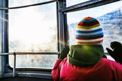 Muchacho en el teleférico que mira hacia fuera la ventana Imágenes de archivo libres de regalías