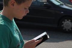 Muchacho en el tráfico que mira el teléfono móvil Foto de archivo libre de regalías