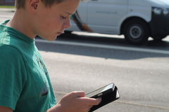 Muchacho en el tráfico que mira el teléfono móvil Fotos de archivo