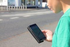 Muchacho en el tráfico que mira el teléfono móvil Fotografía de archivo libre de regalías