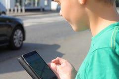 Muchacho en el tráfico que mira el teléfono móvil Fotos de archivo libres de regalías