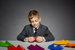 Muchacho en el traje de negocios que hace color los aviones de papel Imágenes de archivo libres de regalías