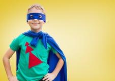 Muchacho en el traje del super héroe que se coloca con sus manos en su cintura Imágenes de archivo libres de regalías