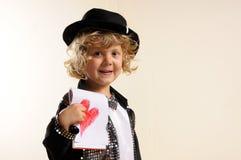 Muchacho en el traje, mostrando un dibujo de un corazón Imágenes de archivo libres de regalías