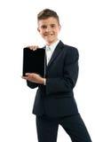 Muchacho en el traje negro que muestra la tableta Foto de archivo