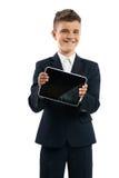 Muchacho en el traje negro que muestra la tableta Fotografía de archivo libre de regalías