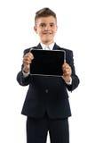 Muchacho en el traje negro que muestra la tableta Imagenes de archivo