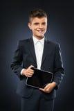 Muchacho en el traje negro que sostiene una tableta Fotografía de archivo