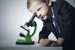 Muchacho en el traje que mira en microscopio Niño elegante poco fondo del scientistGrey Imágenes de archivo libres de regalías