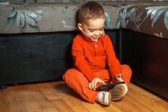 Muchacho en el traje rojo que juega a juegos móviles Imagen de archivo libre de regalías