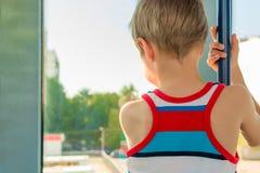 Muchacho en el transporte que mira hacia fuera la ventana Foto de archivo libre de regalías