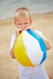 Muchacho en el verano que infla la pelota de playa Foto de archivo libre de regalías