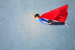 Muchacho en el vuelo rojo del cabo y de la máscara del super héroe en el aire Fotografía de archivo