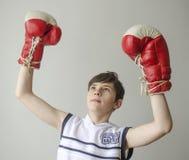 Muchacho en guantes de boxeo con las manos aumentadas en gesto de la victoria Imagen de archivo