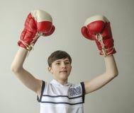 Muchacho en guantes de boxeo con las manos aumentadas en gesto de la victoria Imágenes de archivo libres de regalías
