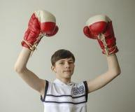 Muchacho en guantes de boxeo con las manos aumentadas en gesto de la victoria Imagenes de archivo
